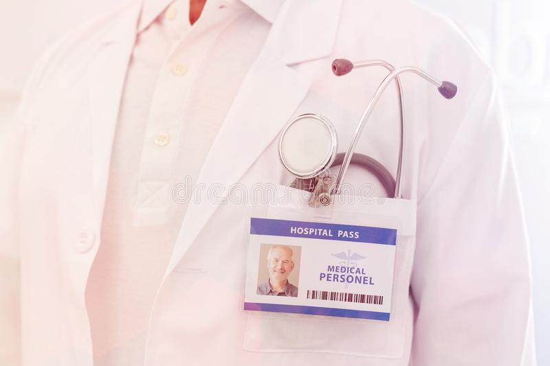 Midsection of senior doctor with identity card and stethoscope at hospital royalty free stock image