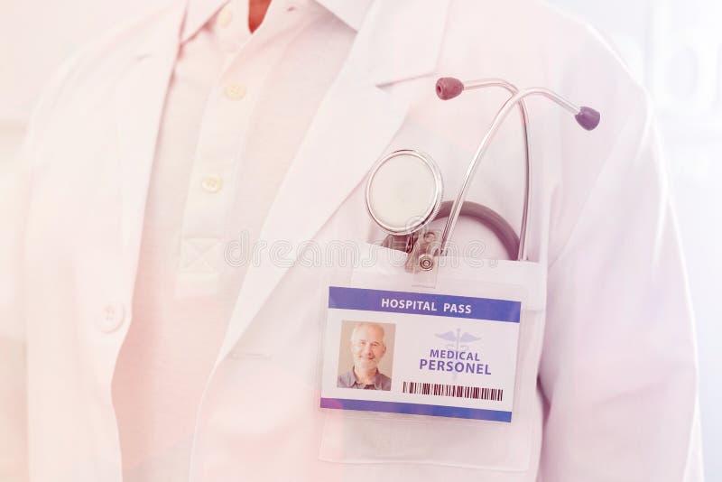 Midsection senior lekarka z dowodem to?samo?ci i stetoskop przy szpitalem obraz royalty free