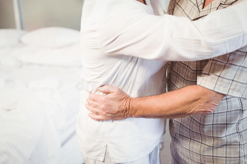 Midsection of senior man embracing wife stock photography