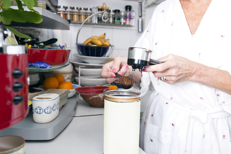 Midsection of senior woman filling ground espresso in portafilter at kitchen counter royalty free stock image