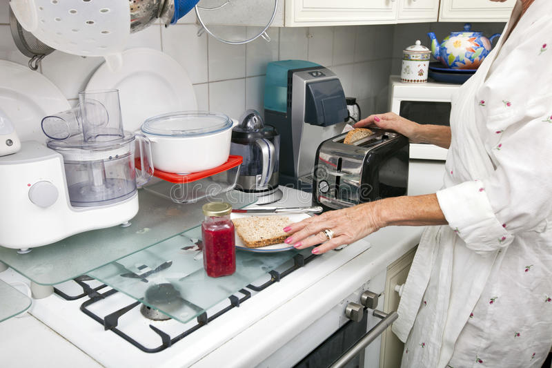 Midsection of senior woman preparing toast at kitchen counter royalty free stock images