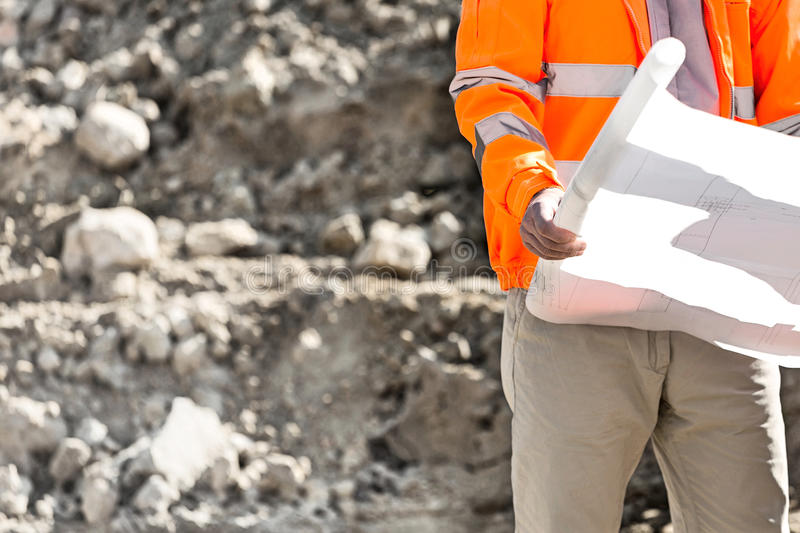 Midsection of supervisor holding blueprint at construction site stock image