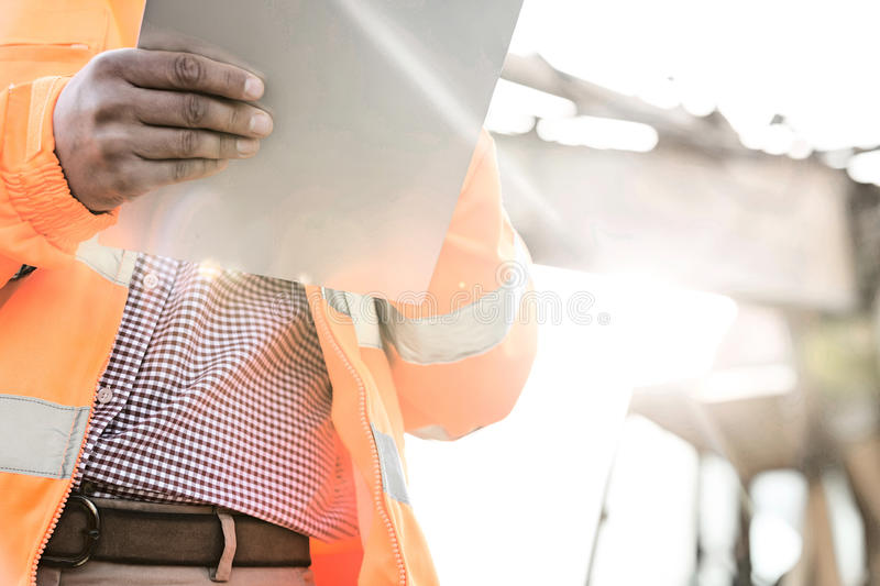 Midsection supervisor holding clipboard at construction site on sunny day royalty free stock photos