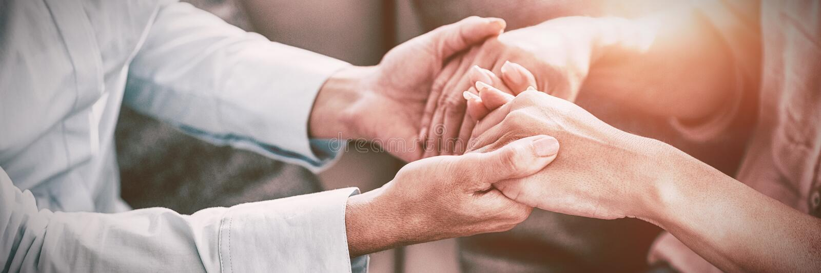 Midsection of therapist holding patient hands royalty free stock image