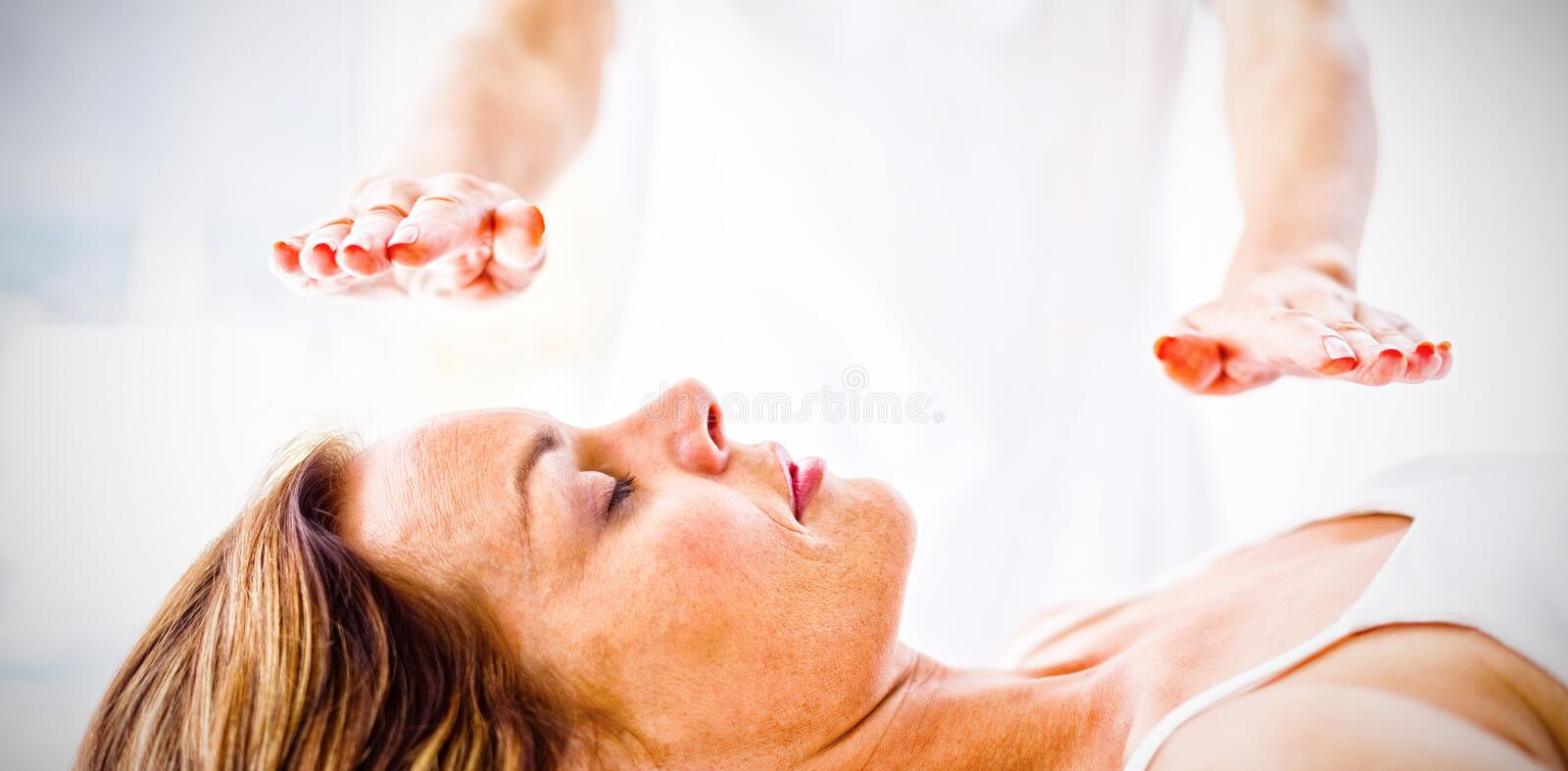 Midsection of therapist performing reiki treatment on woman stock photo