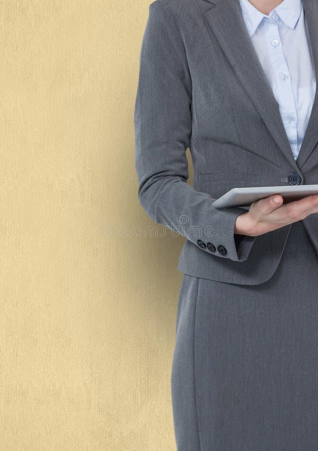 Midsection trzyma cyfrową pastylkę przeciw żółtemu tłu bizneswoman zdjęcia stock