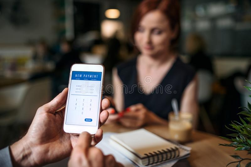 Midsection of businesspeople with smartphone in a cafe, checking finances. stock photo