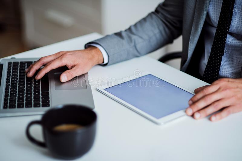A midsection of businessman sitting at the table, using tablet. Copy space. stock images
