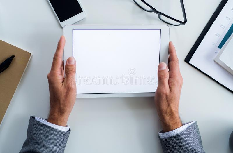 A midsection of businessman sitting at the table, using tablet. A top view. Copy space. stock photos