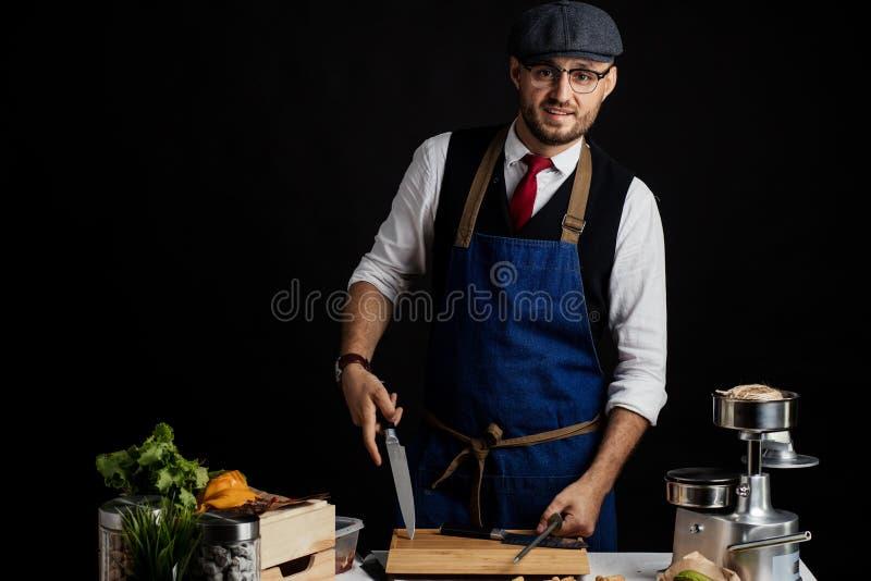 Midsection van de Mannelijke Commerciële Keuken van Chef-koksharpening knife in royalty-vrije stock fotografie
