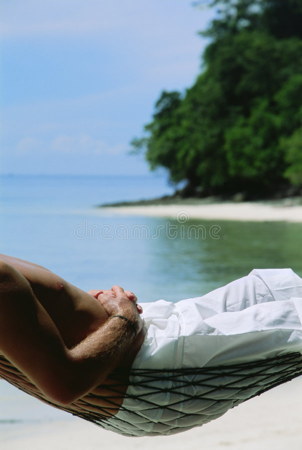 Midsection van de mens die in hangmat bij strand ligt royalty-vrije stock fotografie