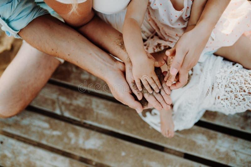 Midsection van familie met een zitting van het peutermeisje op zandstrand op de zomervakantie royalty-vrije stock afbeeldingen
