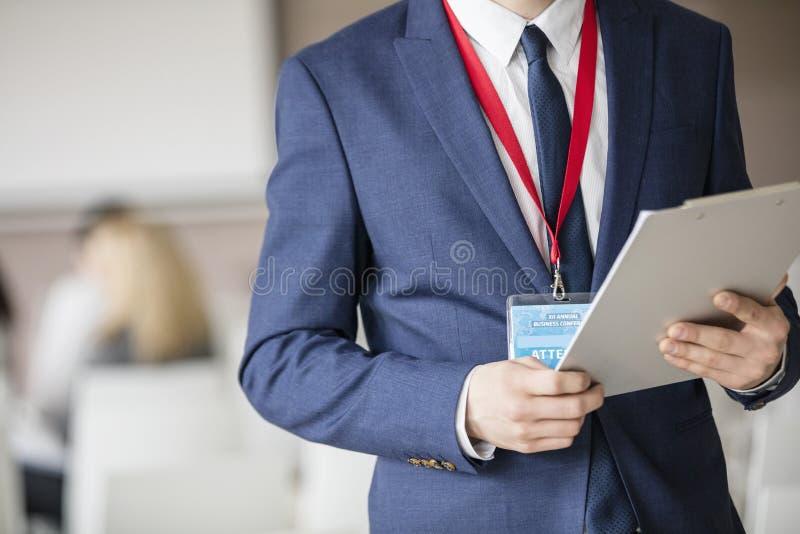 Midsection van het klembord van de zakenmanholding in seminariezaal stock fotografie