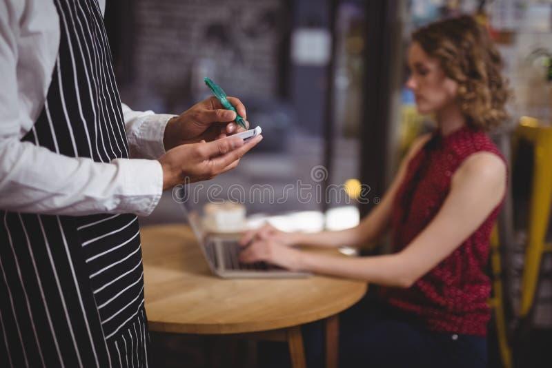 Midsection van kelner het schrijven op blocnote tegen vrouwelijke klantenzitting bij lijst stock afbeeldingen