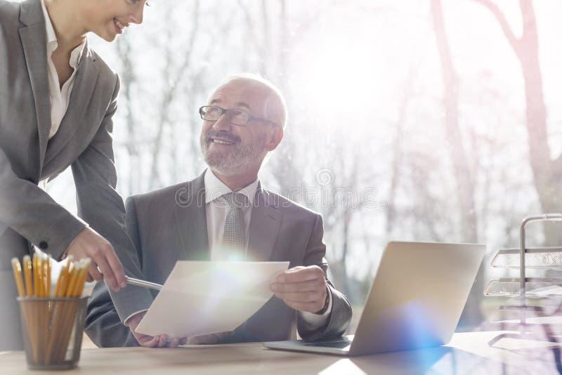 Midsection van onderneemster die over document met glimlachende hogere zakenman bij bureau tegen venster in bureau bespreken stock afbeeldingen