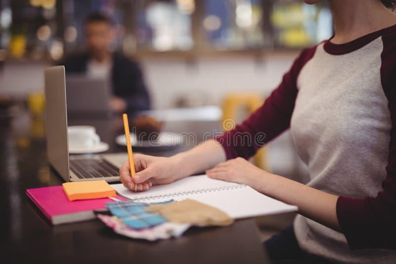Midsection van ontwerp het professionele schrijven in zuivelfabriek bij koffiewinkel royalty-vrije stock afbeeldingen