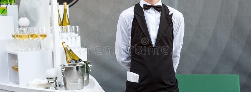 Midsection van professionele kelner in eenvormige dienende wijn tijdens de partij van de buffetcatering, feestelijk gebeurtenis o royalty-vrije stock foto
