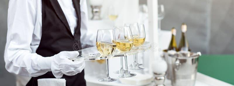 Midsection van professionele kelner in eenvormige dienende wijn tijdens de partij van de buffetcatering, feestelijk gebeurtenis o royalty-vrije stock afbeeldingen