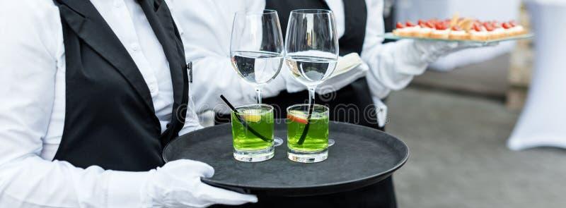 Midsection van professionele kelners in eenvormige dienende wijn, cocktails en snacks tijdens de feestelijke partij van de buffet stock afbeelding