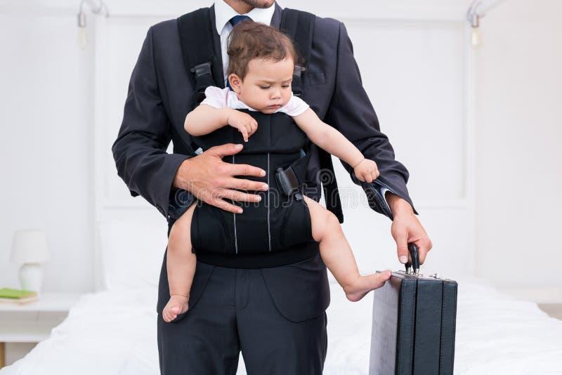 Midsection van vader dragende baby terwijl het houden van aktentas stock foto
