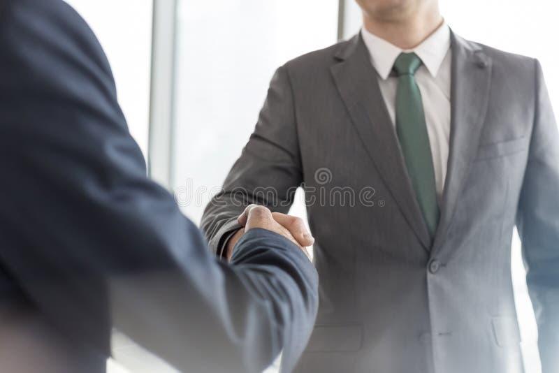 Midsection van zakenlieden die handen schudden terwijl status in bestuurskamer tijdens vergadering op kantoor stock foto's
