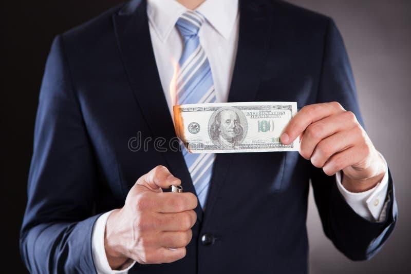 Midsection van zakenman brandend geld stock afbeeldingen