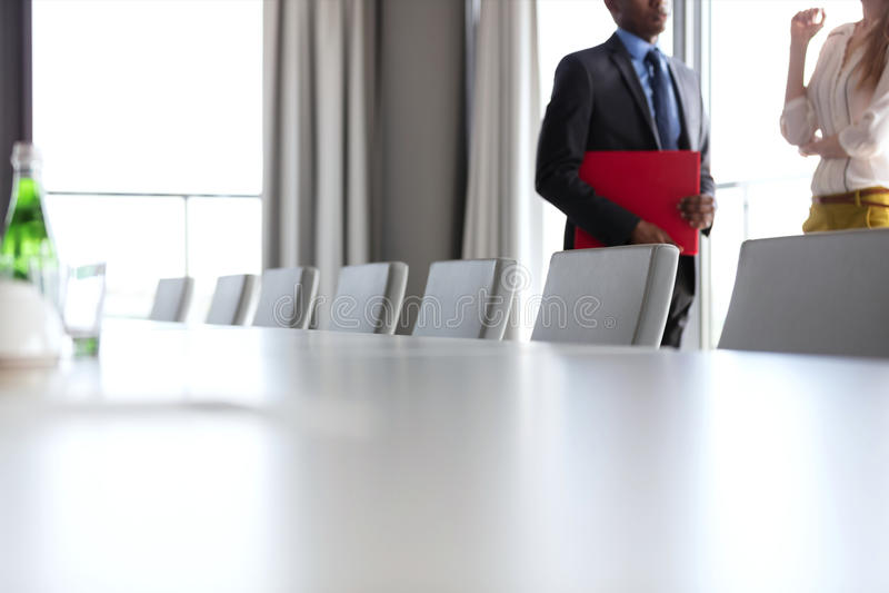 Midsection van zakenman en onderneemster die zich door conferentielijst bevinden in bureau stock fotografie