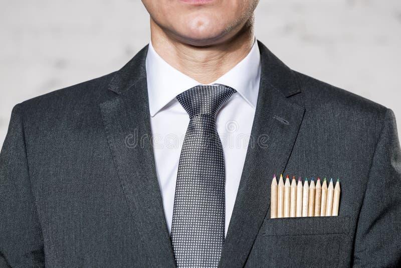 Midsection van zakenman met kleurpotloden in zak tegen muur royalty-vrije stock afbeeldingen
