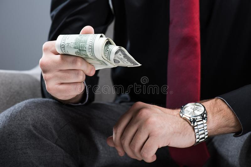 Midsection van zakenmanzitting in leunstoel en holdingsgeld ter beschikking, stock foto