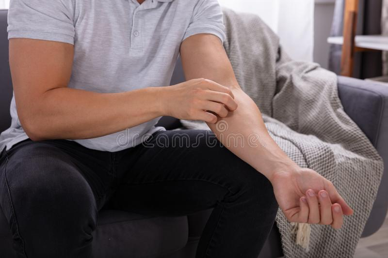 Man Suffering From Itching. Midsection View Of A Man Sitting On Sofa Suffering From Itching royalty free stock image