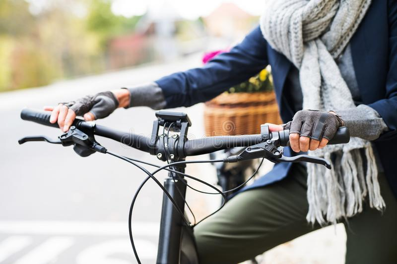 A midsection of senior woman with electrobike outdoors in town. stock photos
