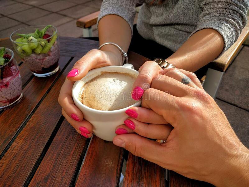 Midsection of Woman Holding Coffee Cup on Table stock images