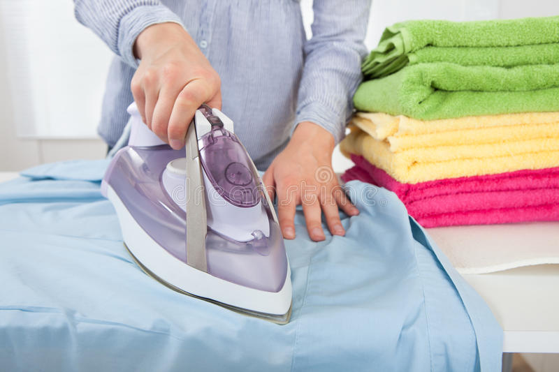 Midsection Of Woman Ironing Shirt stock image