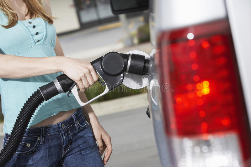 Midsection Of A Woman Refueling Her Car royalty free stock images