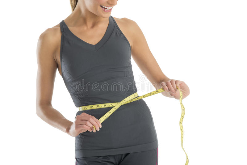 Download Midsection Woman Smiling While Measuring Her Waistline Stock Image - Image: 32278563