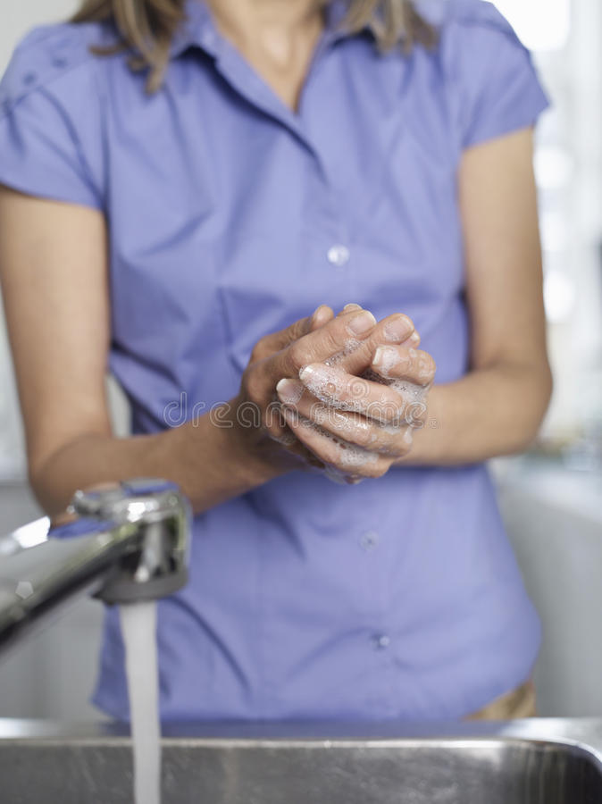 Midsection Of Woman Washing Hands In Sink royalty free stock photo