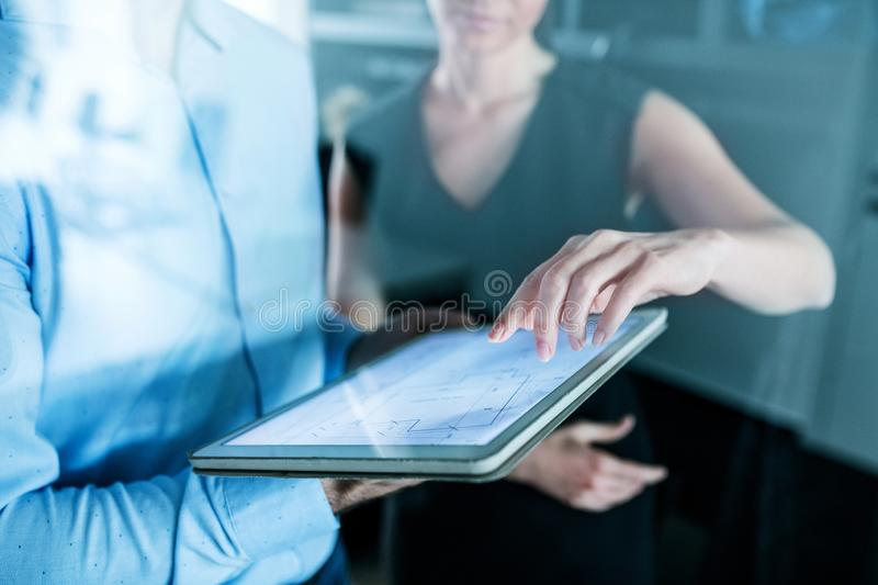 Midsection of young businesspeople with tablet in an office, working. stock photos
