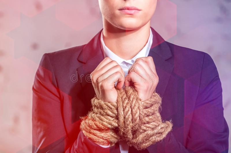 Young businesswoman standing with tied hands at office. Midsection of young businesswoman standing with tied hands at office royalty free stock photography