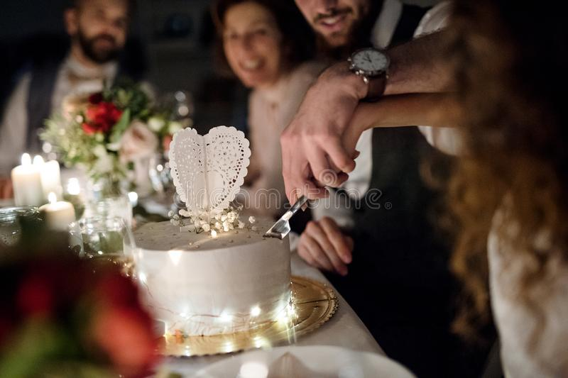 A midsection of young couple sitting at a table on a wedding, cutting a cake. stock image