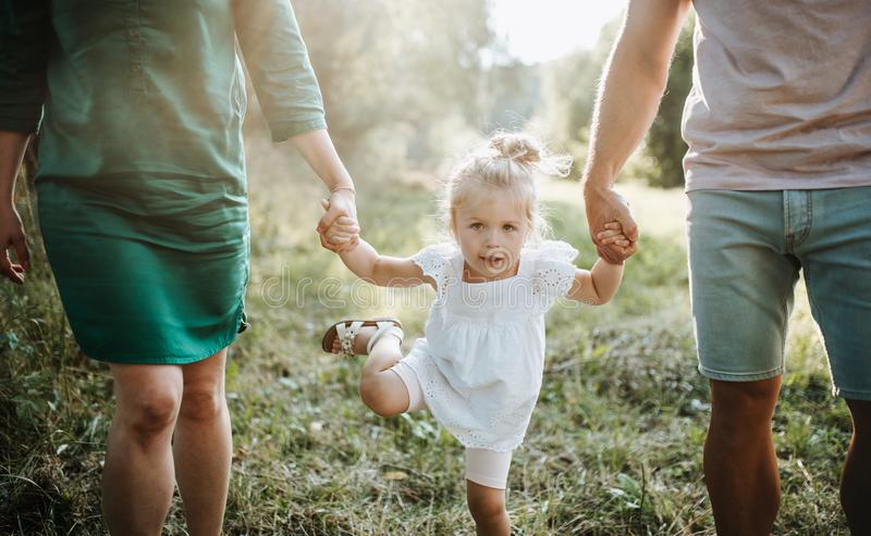 A midsection of young family with a small daughter walking in sunny summer nature. stock image