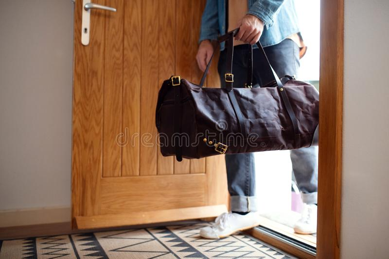 Midsection of young man with bag entering front door when coming back home. A midsection of young man with bag entering front door when coming back home stock photo