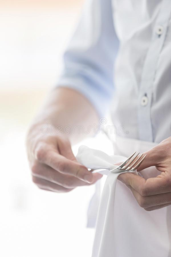 Midsection of young waiter cleaning fork in restaurant royalty free stock image