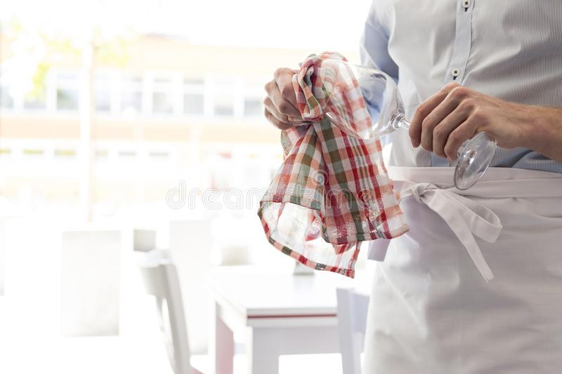 Midsection of young waiter cleaning wineglass in restaurant royalty free stock photography
