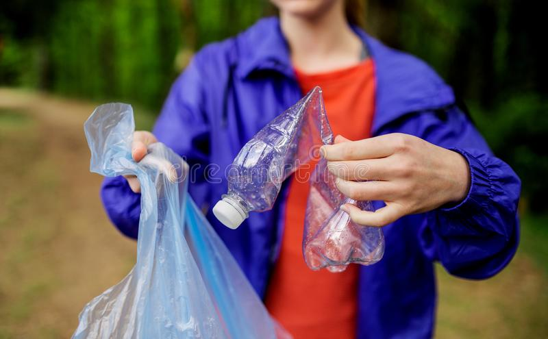 Midsection of young woman picking up litter in nature, a plogging concept. royalty free stock photos