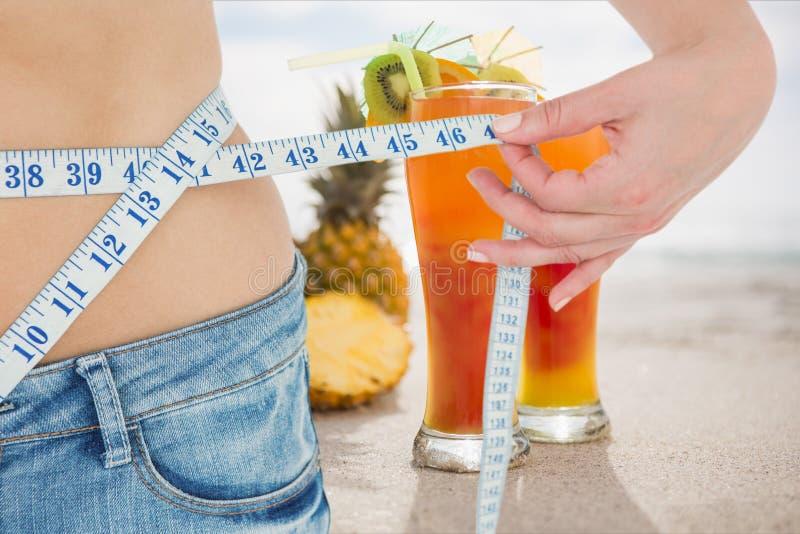 Midsectionavsnitt av kvinnan som mäter midjan med fruktsafter i bakgrund royaltyfri bild