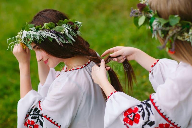 midsummer Deux filles dans les v?tements slaves tissent des tresses dans les cheveux pr?s du feu photographie stock
