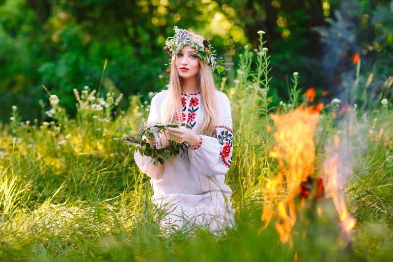 midsummer Kobieta wyplata wianek blisko ogienia obrazy stock