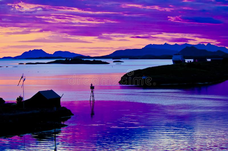 Midsummer night in Norway, colorful sky, reflecting in sea. Midsummer night in North Norway. Sky with ultra violet colors reflecting in North Sea stock photos