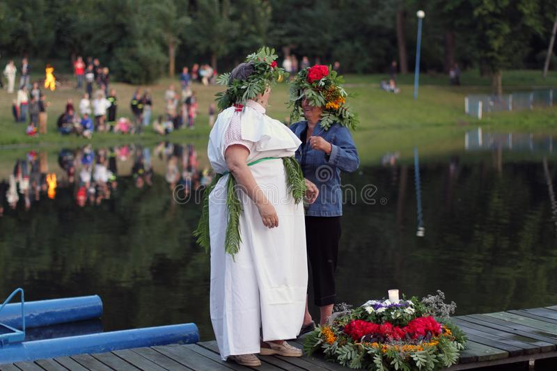 Two women let go garlands for water, Poniatowa, 06.2011, Poland. Midsummer Nights, releasing wreaths on water, bonfire, folk tradition, colorful garlands float stock photos