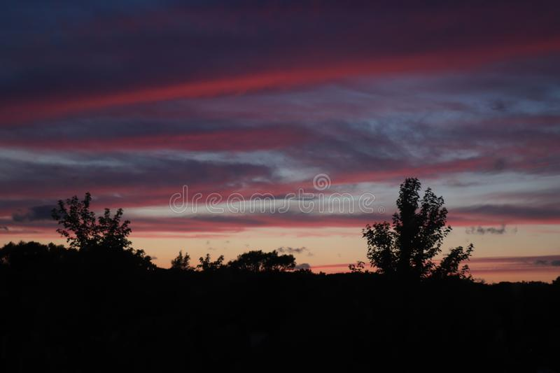 Midsummer sunset sky. Colorful midsummer sunset sky with silhouettes of trees stock images